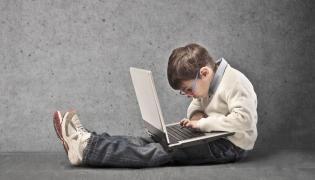 Dziecko z laptopem na kolanach
