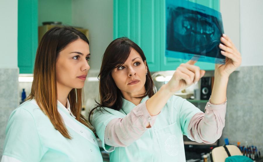 Stomatolog pokazuje pacjentce RTG zębów