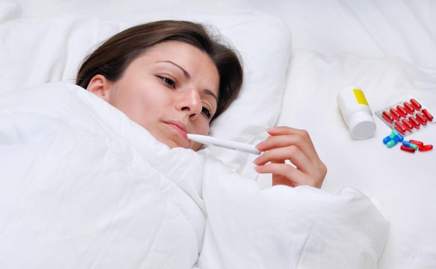 Chora kobieta mierzy temperaturę