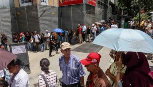 Ludzie w kolejce do banku w Caracas