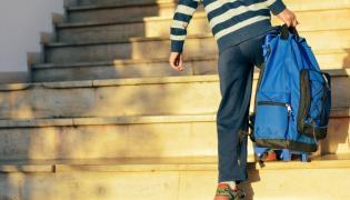 Chłopiec z plecakiem na kółkach