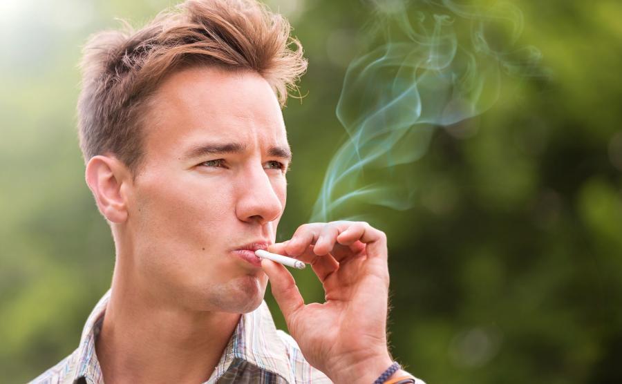 Mężczyzna pali papierosa