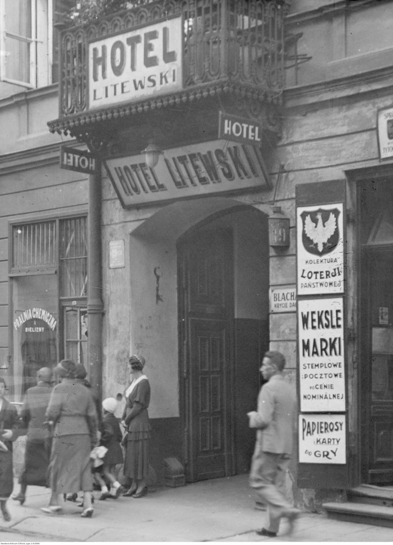 Fragment budynku z wejściem do hotelu przy ulicy Chmielnej 19. Widoczne szyldy reklamowe / 1932 rok
