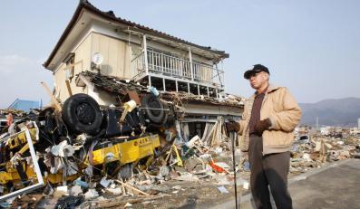 Mężczyzna stoi obok zdewastowanego domu w Ofunato w prefekturze Iwate w północnej Japonii