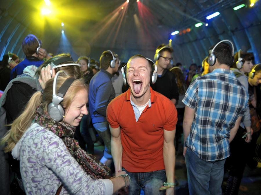 Zabawa w hangarze Silent Disco przy muzyce, którą słychać tylko przez słuchawki
