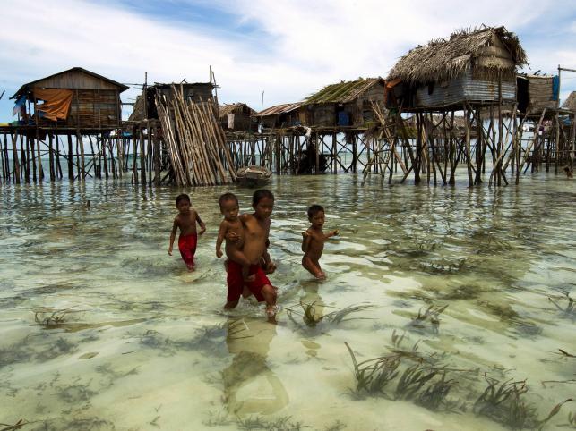 Dzieci poczas odpływu w wiosce  wybrzeża wyspy Omadal