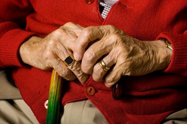 Emeryt trzyma laskę w dłoniach