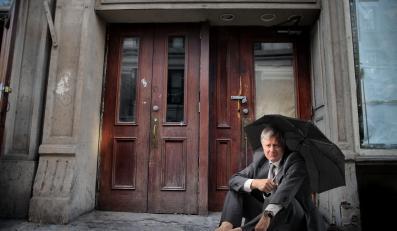Bezdomny bezrobotny bankrut siedzi parasolem przed kamienicą