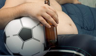 Kibic z dużym gołym brzuchem i piwem ogląda mecz piłkarski
