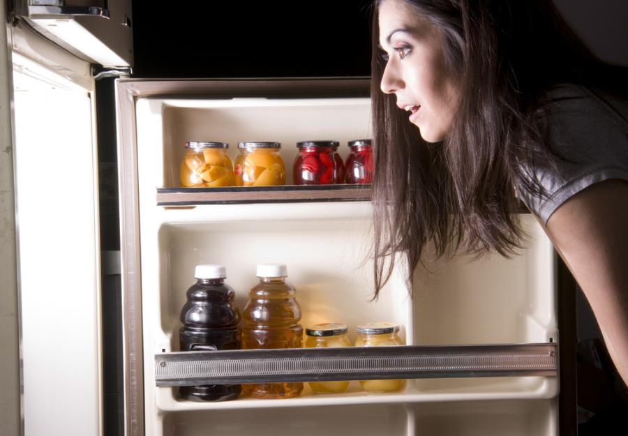 Kobieta zagląda do lodówki - zdjęcie ilustracyjne