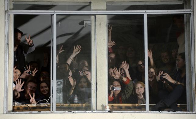 Widzowie obserwujący czerwony dywan przez okno