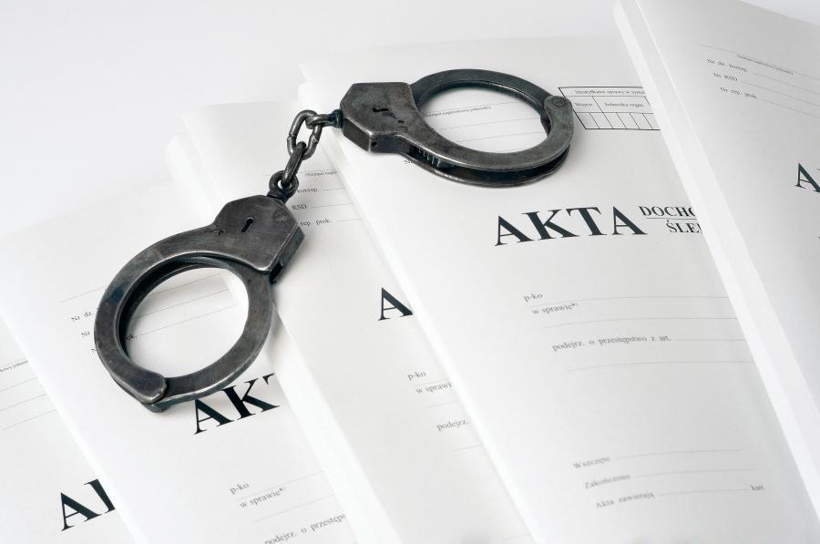 Akta śledztwa i kajdanki