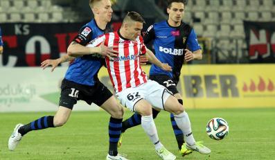 Zawodnik Cracovii Erik Jendrisek (C) walczy o piłkę z Jakubem Wójcickim (L) i Cornelem Predescu (P) z Zawiszy Bydgoszcz
