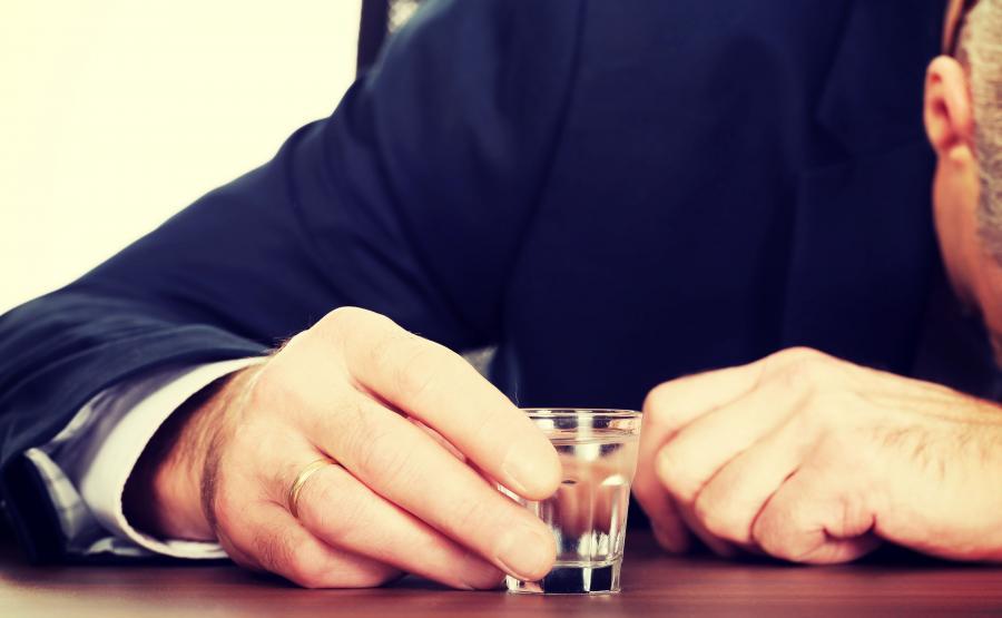 Pijany mężczyzna trzyma kieliszek wódki